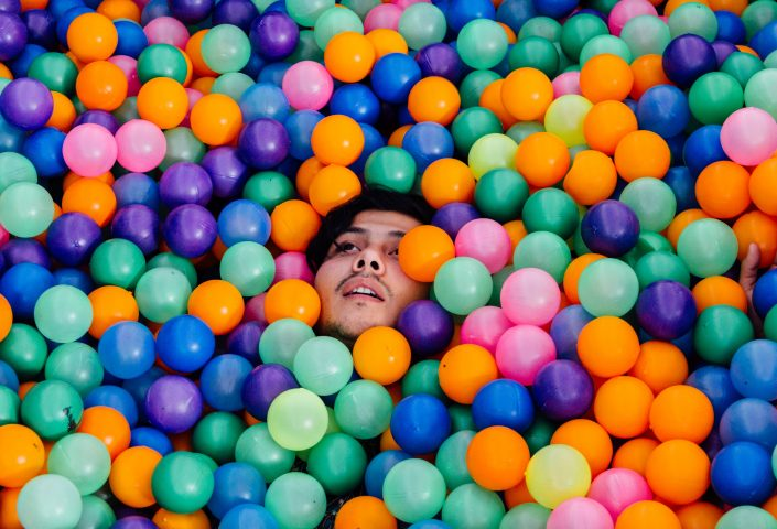 Head-inside-pool-of-colorful-balls